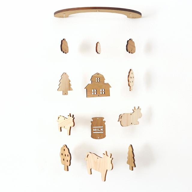 壁にかけられる木のモビール(牛と牧場)