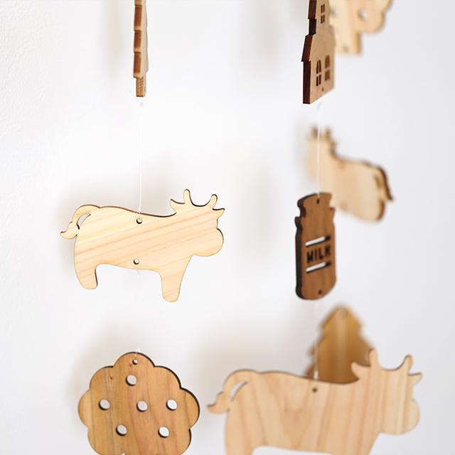 壁にかけられる木のモビール牛と牧場のアップ画像